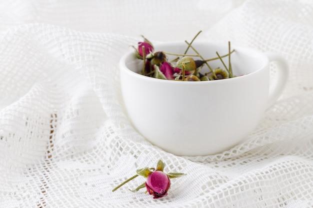 Blumentee-rosenknospen auf altem holztisch