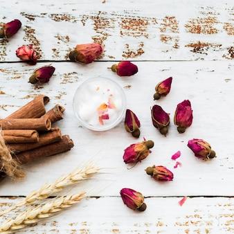 Blumentee von rosenknospen; zimtstangen; baumwolle in der schüssel; garbe weizenähren auf hölzerner planke der weißen beschaffenheit