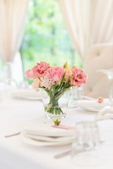 Blumentischdekorationen für feiertage und hochzeitsabendessen. tabelle stellte für feiertagshochzeitsempfang restaurant im im freien ein.
