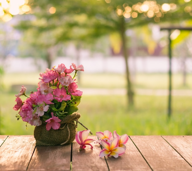 Blumentopf auf holztisch mit blick auf den garten