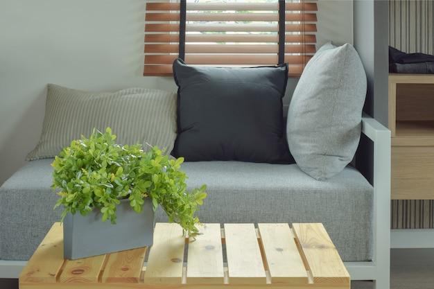 Blumentopf auf mittlerem holztisch und bequemem sitz im wohnzimmer