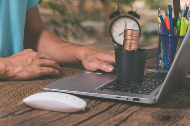 Blumentopf voller münzen auf laptop-tastatur