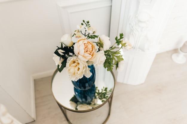 Blumenvase auf einem spiegeltisch in einem weißen hellen wohnzimmer
