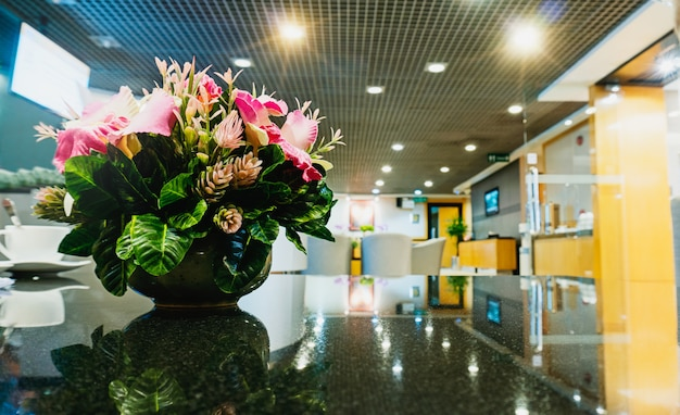 Blumenvase auf tabelle im lobbybereich mit kopienraum