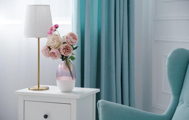 Blumenvase und goldene tischlampe mit blauem sessel und vorhängen