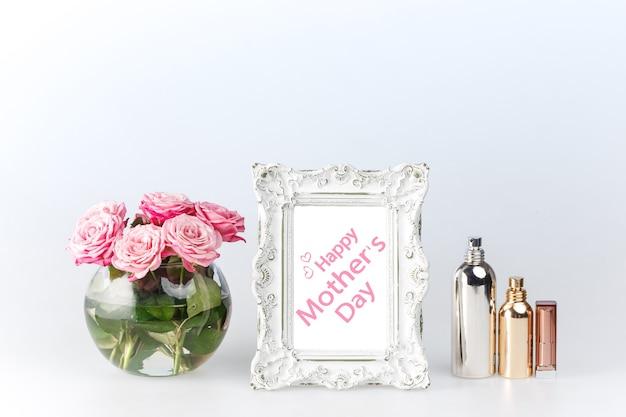 Blumenvase und weißer bilderrahmen der weinlese und parfüm auf weiß. glückliches muttertagskonzept