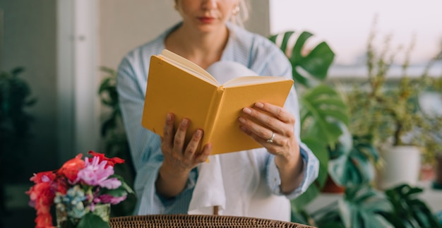 Blumenvase vor der jungen frau, die das gelbe buch liest