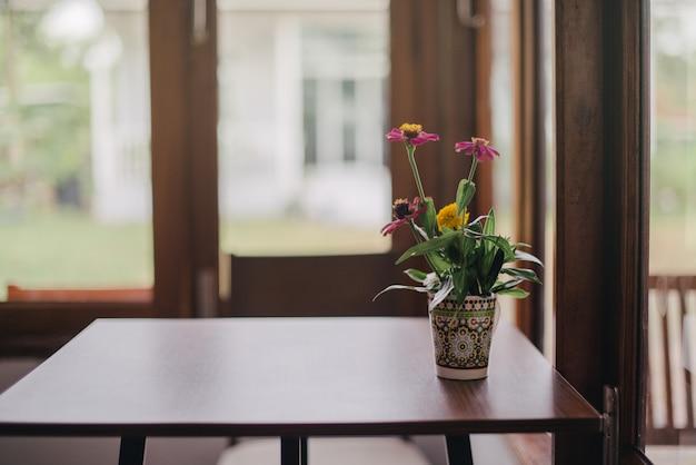 Blumenvasen stellten am fenster in einer weinlesekaffeestube ein