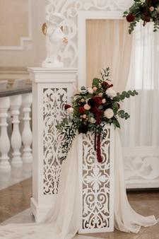 Blumenzusammensetzung auf dem weißen bogen in der hochzeitszeremoniehalle