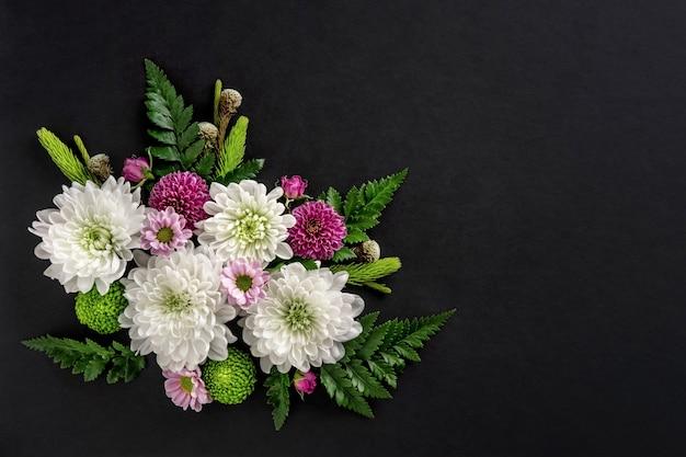 Blumenzusammensetzung der bunten blumenchrysantheme lokalisiert auf schwarzem hintergrund. sommerkranz aus chrysanthemenblüten. flach liegen.