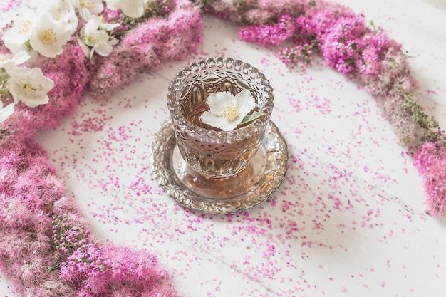 Blumenzusammensetzung. kreis aus rosa blüten mit einem glas tee auf weiß