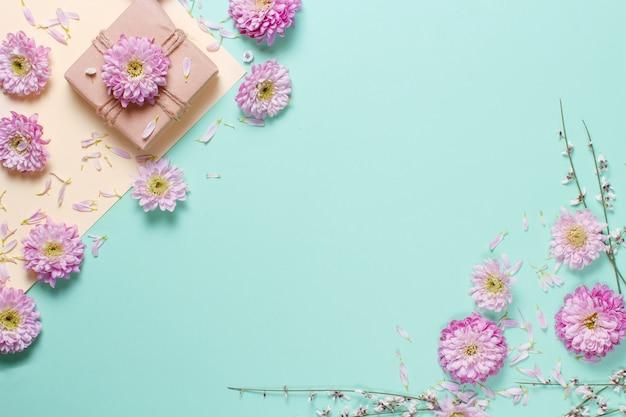 Blumenzusammensetzung mit blumen und geschenkbox auf einem pastellhintergrund