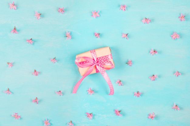 Blumenzusammensetzung. muster aus rosa kirschblütenblumen mit geschenkbox auf blauem hölzernem hintergrund. flach liegen