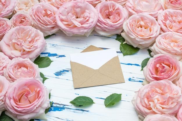 Blumenzusammensetzung. öffnen sie den umschlag im rahmen aus rosa rosen auf gealtertem holz.