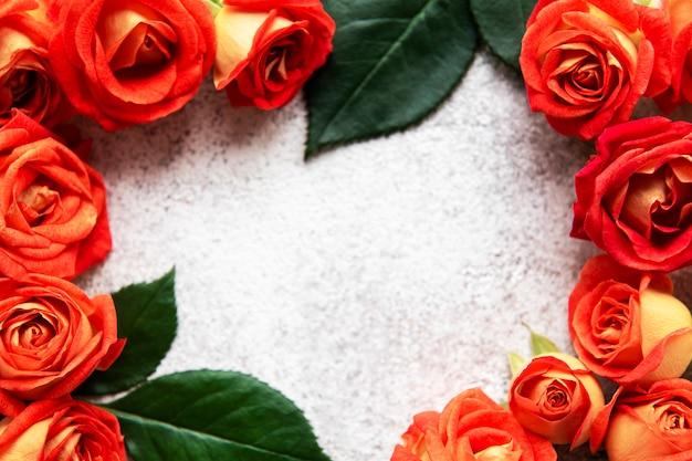 Blumenzusammensetzung rahmen aus roten rosen und blättern auf betonhintergrund