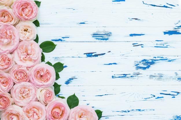 Blumenzusammensetzung. rosa rosen auf gealtertem weißem holz.