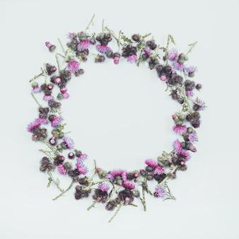 Blumenzusammensetzung. runder rahmen aus grünen distelzweigen mit dornen und blühenden zarten purpurroten blüten.