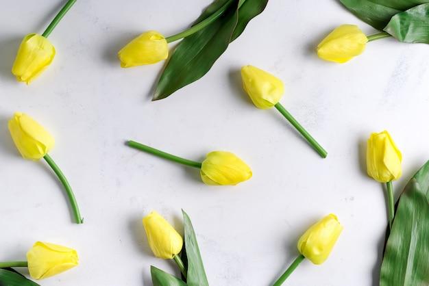 Blumige gelbe tulpe auf marmoroberfläche. flache lage, draufsicht.