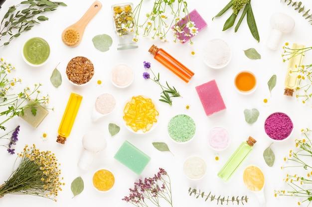 Blumiger hintergrund der spa-aromatherapie, flache lage verschiedener schönheitspflegeprodukte, verziert mit einfachen kamillenblüten.