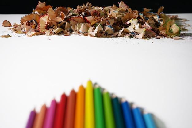 Blur bunter hölzerner zeichenstift staplungs- und anspitzerfarbbleistift auf papier.