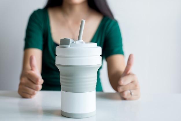 Blured frau, die daumen oben mit wiederverwendbarer kaffeetasse zeigt