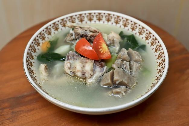 Blurry selective focus tasty sop ayam hühnersuppe mit fleischbällchen und tomaten-kirsche obenauf