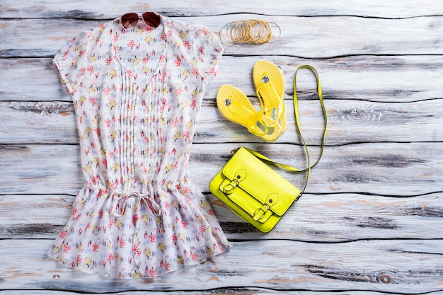Bluse, flip-flops und geldbörse. helle bluse und limettentasche. damen-outfit mit hellem accessoire. sommerkleidung zum kleinen preis.