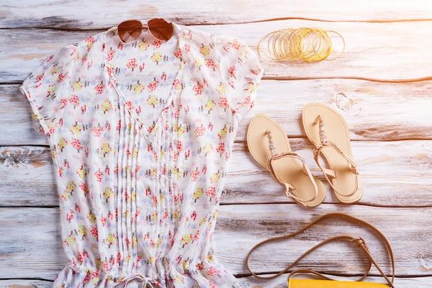 Bluse mit v-ausschnitt und hellem muster. bluse, sandalen und sonnenbrille. kleidung auf weißer holzvitrine. brandneue kleidung für damen.