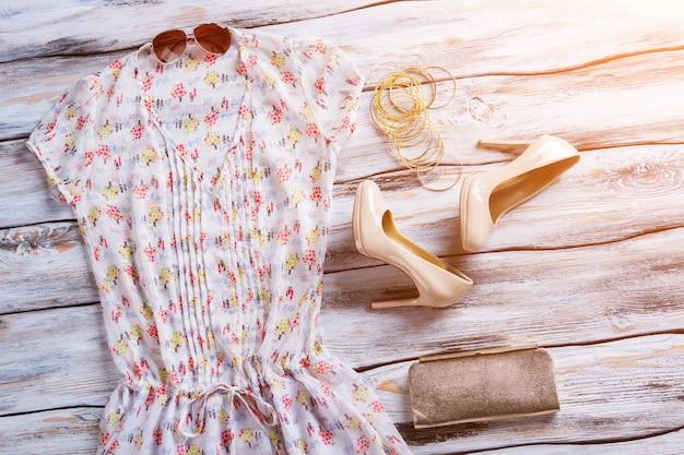 Bluse, sonnenbrille und absatzschuhe. bluse mit v-ausschnitt und armbandset. damenbekleidung mit stylischem muster. qualitätskleidung zum kleinen preis.