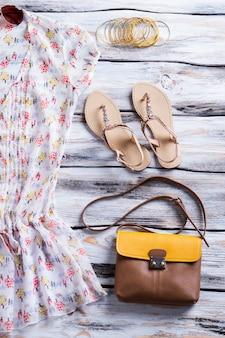 Bluse und geldbörse mit sandalen. weißes top mit buntem muster. casual outfit des mädchens auf dem display. leichte baumwolle und hochwertiges leder.