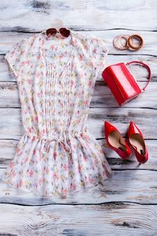 Bluse und rote fersenschuhe. leuchtend rote handtasche mit bluse. attraktive kleidung des mädchens auf schaukasten. sonderrabatte im modegeschäft.