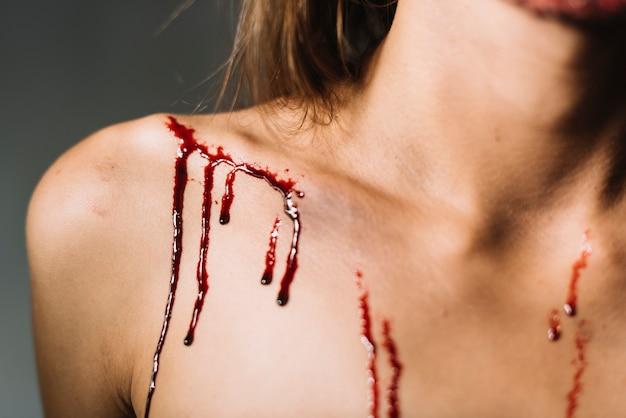 Blut spritzt auf die schulter der jungen frau