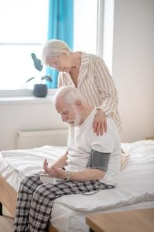Blutdruck. grauhaarige ältere frau, die ihrem ehemann hilft, den blutdruck zu überprüfen