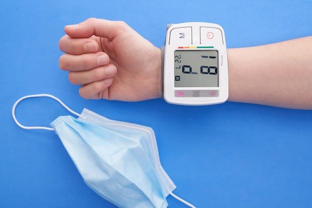 Blutdruckmessgerät auf blauem hintergrund und operationsmaske