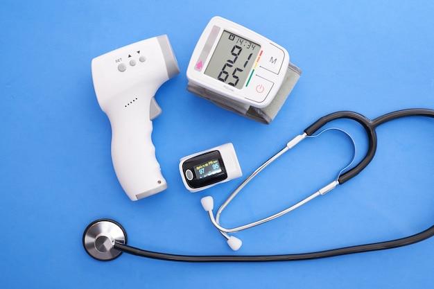 Blutdruckmessgerät, oximeter, digitales thermometer und stethoskop auf blauem hintergrund