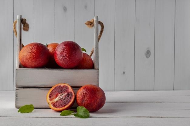 Blutige orangen in kiste auf weißem holztisch, leerer raum. frische zitrusfrüchte