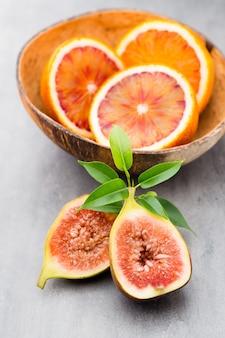 Blutige sizilianische orangen und feigen auf grauem tisch