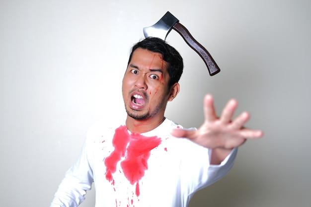 Blutiger mann, der schreit, während er eine axt in seinem kopf steckt. halloween-konzept