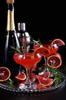 Blutiger orangen-zitrus-champagner-cocktail. köstliches, edles getränk, das jeder auf ihrer party lieben wird