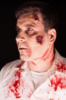 Blutiger zombie auf schwarzem hintergrund hautnah. gruseliger mann. kreatives make-up.