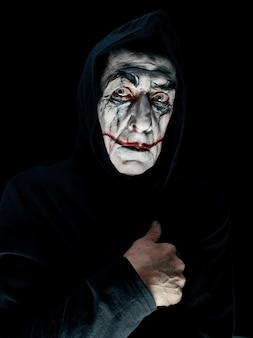 Blutiges halloween-thema: das verrückte maniak-gesicht im dunklen studio