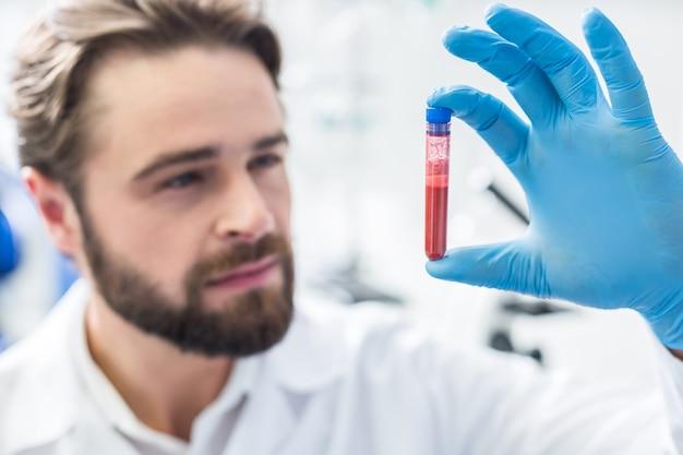 Blutprobe. selektiver fokus eines reagenzglases mit blut, das von einem netten, intelligenten, professionellen laboranten gehalten wird