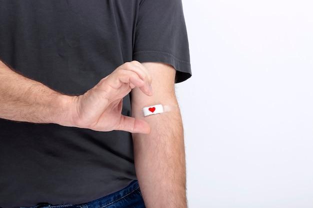 Blutspende. mann in grauer t-shirt hand mit patch mit rotem herzen geklebt, nachdem blut auf grauer wand gegeben wurde. zeigt ein halbes herz mit seiner hand. speicherplatz kopieren