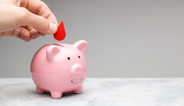Blutspender. ein mann hält einen roten blutstropfen in der hand und legt ihn als spende in ein sparschwein. grauer hintergrund