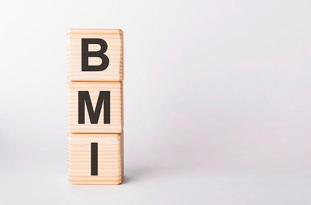 Bmi-buchstaben von holzklötzen in säulenform auf weiß