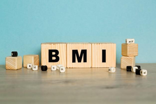 Bmi-wort aus holzbuchstaben auf blauem hintergrund