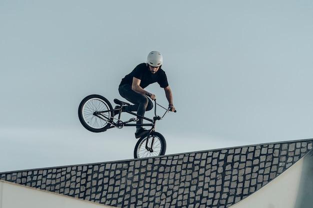 Bmx-fahrer, der einen umgekehrten wheelie auf steinziegel-fahrradpark macht