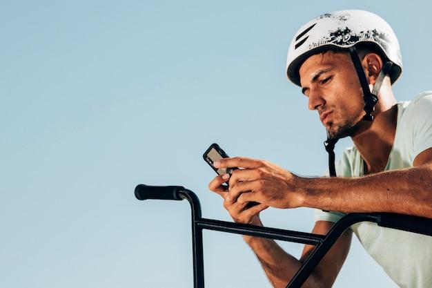 Bmx mitfahrer, der seinen mittleren schuß des telefons betrachtet