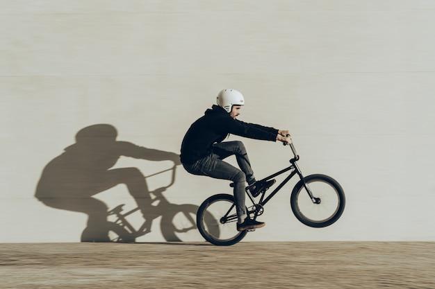 Bmxer macht einen wheelie mit seinem schatten, der in eine steinmauer projiziert wird