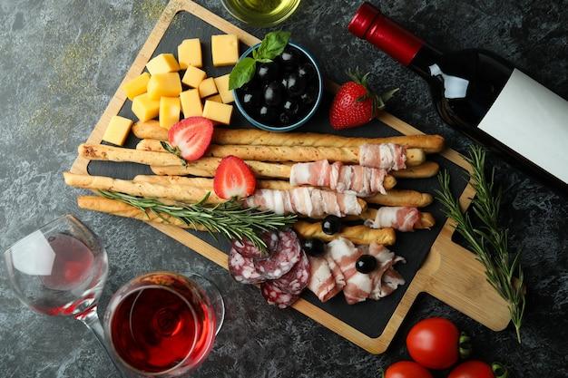 Board mit grissini und snacks und wein auf schwarzer rauchiger oberfläche